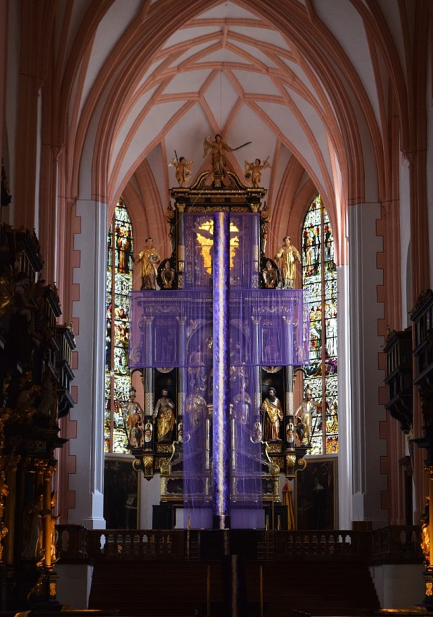 The catacomb saints in Mondsee are obscured by a purple crucifix.